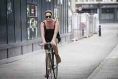 Poważna dziewczyna w czarnej sukni z krzyżować drogę na bicyklu Obrazy Royalty Free