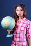 Poważna dziewczyna w szkockiej kraty koszula trzyma kulę ziemską. fotografia royalty free