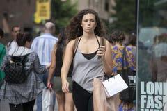 Poważna dziewczyna z kędzierzawego włosy odprowadzenia puszkiem ulica Obrazy Stock