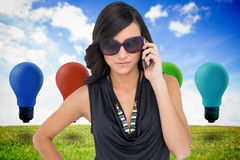 Poważna elegancka brunetka jest ubranym okulary przeciwsłonecznych na telefonie Zdjęcia Stock