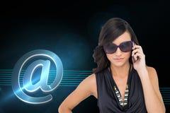 Poważna elegancka brunetka jest ubranym okulary przeciwsłonecznych na telefonie Obraz Stock