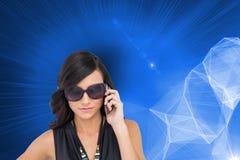 Poważna elegancka brunetka jest ubranym okulary przeciwsłonecznych na telefonie Obraz Royalty Free
