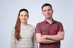 Poważna europejska para stoi wpólnie na szarej studio ścianie zdjęcie royalty free