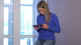 Poważna kobieta używa cyfrową pastylkę w hotelowym lobby podczas gdy siedzący na walizce zdjęcie wideo