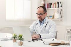 Poważna lekarka pisać na maszynie na laptopie w szkłach zdjęcia stock