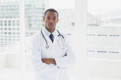 Poważna lekarka z rękami krzyżował w medycznym biurze Fotografia Stock