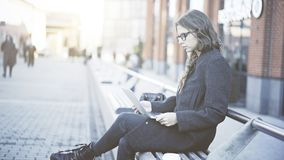 Poważna młoda kobieta patrzeje jej laptop w ulicie w szkłach Zdjęcia Royalty Free