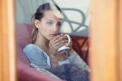 Poważna młoda kobieta patrzeje przez okno podczas gdy pijący kawę na kanapie w domu obraz stock