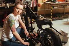Poważna młoda kobieta podczas gdy siedzący pobliski jej rower Zdjęcie Stock
