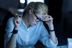 Poważna młoda kobieta pracuje z papierami w biurze fotografia royalty free