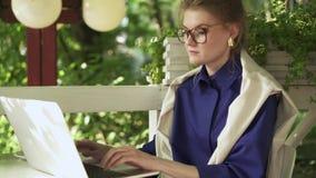 Poważna młoda kobieta w szkła działaniu z laptopem w lato kawiarni zdjęcie wideo