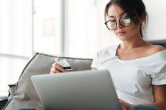 Poważna młodej kobiety mienia karta debetowa używać laptop Obraz Royalty Free