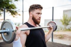 Poważna młody człowiek atlety pozycja i mienia barbell Obrazy Royalty Free