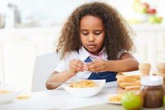Poważna mała dziewczynka ma lunch Obrazy Stock