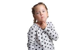 Poważna mała dziewczynka z poważnym spojrzeniem, spojrzenia przed ona z ręką blisko gardła pojedynczy białe tło obraz royalty free