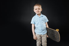 Poważna mała męska osoba pozuje z deskorolka Fotografia Stock