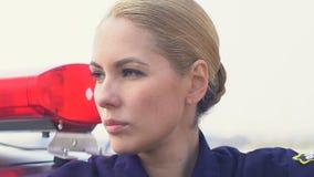 Poważna milicyjna dama stoi blisko radiowozu i patrzeje na boku, prawo ochrona zdjęcie wideo