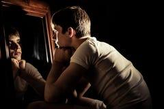 Poważna nastoletnia chłopiec patrzeje go w lustrze Zdjęcie Stock
