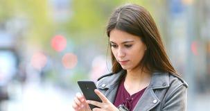 Poważna nastoletnia wyszukuje mądrze telefon zawartość plenerowa zbiory