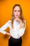 Poważna sfrustowana młoda piękna biznesowa kobieta na pomarańczowym tle Zdjęcie Royalty Free