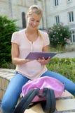 Poważna studencka dziewczyna używa pastylkę outdoors fotografia stock