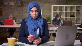 Poważna twarz amuslim kobieta w błękitnym pięknym hijab scrolling jej telefon podczas gdy siedzący w nowożytnym studiu, otaczając