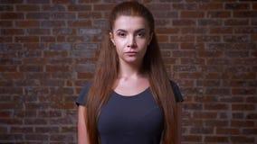 Poważna twarz patrzeje kamerę śliczna miedzianowłosa żeńska patrzeje kamera prosto i stojący blisko brąz ściany z cegieł,