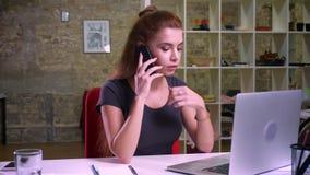 Poważna woking caucaisna imbirowa kobieta jest siedząca i opowiadająca nad telefonem komórkowym podczas gdy oglądający ekran jej
