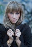 Poważne piękne blond z włosami kobiety pozuje przeciw błękitowi malującemu starzeli się ścianę Zdjęcia Stock