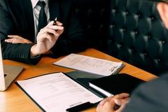 Poważnego azjatykciego biznesmena znacząco rozmowa z męskim pracownikiem przegląda życiorysów dokumenty zdjęcia royalty free