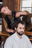 poważnego fryzjera męskiego zgrzywiony włosy klient z hairdryer zdjęcia royalty free