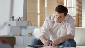 Poważnego w średnim wieku mężczyzny odliczający pieniądze, planuje budżet dla hipoteki, użyteczność zdjęcie royalty free