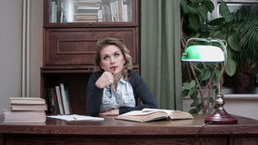 Poważnej kobiety myślący sittnig przy pracy biurkiem z książkami zdjęcie wideo
