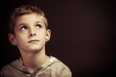 Poważnej młodej chłopiec siedzący główkowanie Zdjęcie Royalty Free