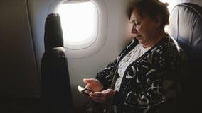 Poważnej starszej samolotowej pasażerskiej kobiety pisać na maszynie wiadomości na smartphone gona app obsiadaniu na samolotowym  zbiory