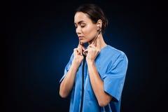 Poważnej ufnej damy słuchający stetoskop odizolowywający Zdjęcia Royalty Free