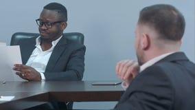 Poważni amerykan biznesmeni pracuje przez papierów i dyskutuje pieniężnego raport z jego partnerem Fotografia Royalty Free