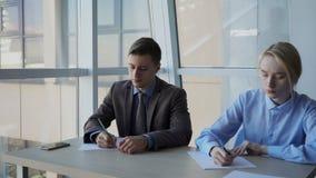 Poważni ludzie biznesu przy stołową kontur informacją na prześcieradłach papier zdjęcie wideo