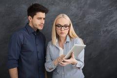 Poważni partnery biznesowi używa cyfrową pastylkę przy studiiem obraz royalty free