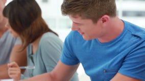 Poważni przyjaciele siedzi podczas gdy robić ich pracie domowej zdjęcie wideo