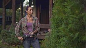 Poważni w średnim wieku azjatykci kobiety podlewania drzewa od węża elastycznego zbiory