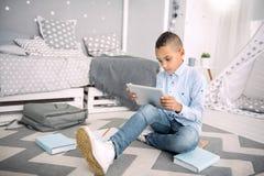 Poważnie ładny chłopiec zwijanie w online uczenie Zdjęcia Royalty Free