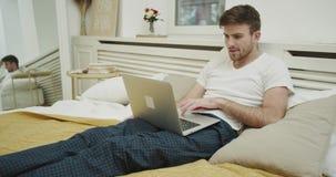 Poważnie obsługuje działanie na jego laptopu obsiadaniu na jego łóżku zbiory