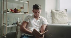Poważnie osobistego czas mężczyzna czyta książkowego obsiadanie na kanapie w ranku, dopatrywanie na okno, wygodnym zdjęcie wideo