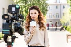 poważny anchorwoman z mikrofon pozycją przed cyfrowym zdjęcia stock