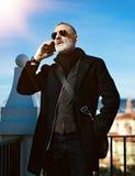 Poważny atrakcyjny mężczyzna jest ubranym czarną kurtkę i opowiada przy telefonem komórkowym podczas gdy wydający czas w miasto p Obrazy Royalty Free