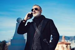 Poważny atrakcyjny mężczyzna jest ubranym czarnych lotników okulary przeciwsłonecznych i opowiada przy telefonem komórkowym podcz Zdjęcia Stock