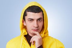 Poważny atrakcyjny młody brunet mężczyzna patrzeje pewnie w kamerę, rozważnego wyrażenie, utrzymanie palec na podbródku, jest ubr Obraz Stock