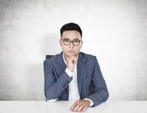 Poważny Azjatycki biznesmen przy stołem, beton Obraz Stock