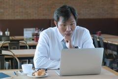 Poważny Azjatycki biznesmen używa laptop przy kawą podczas gdy siedzący Obrazy Stock